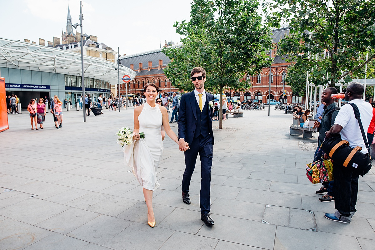 Bride and groom stroll through Kings Cross en route to a Shoreditch warehouse Wedding. Image by Parrot & Pineapple Wedding Photography.