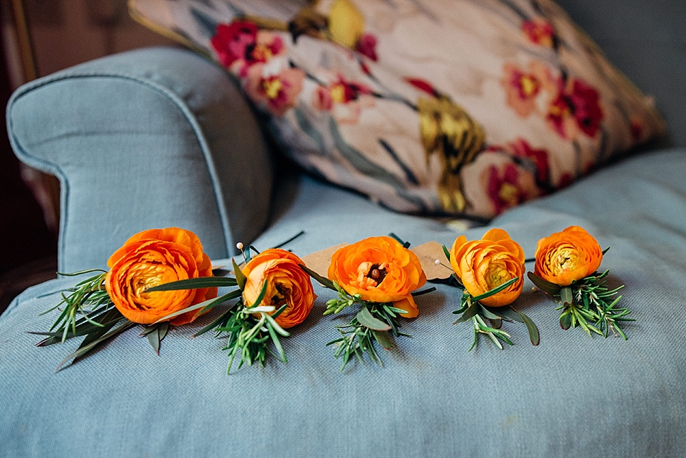 Orange ranunculus button holes. Image by london wedding photographer Parrot and Pineapple Wedding Photography.