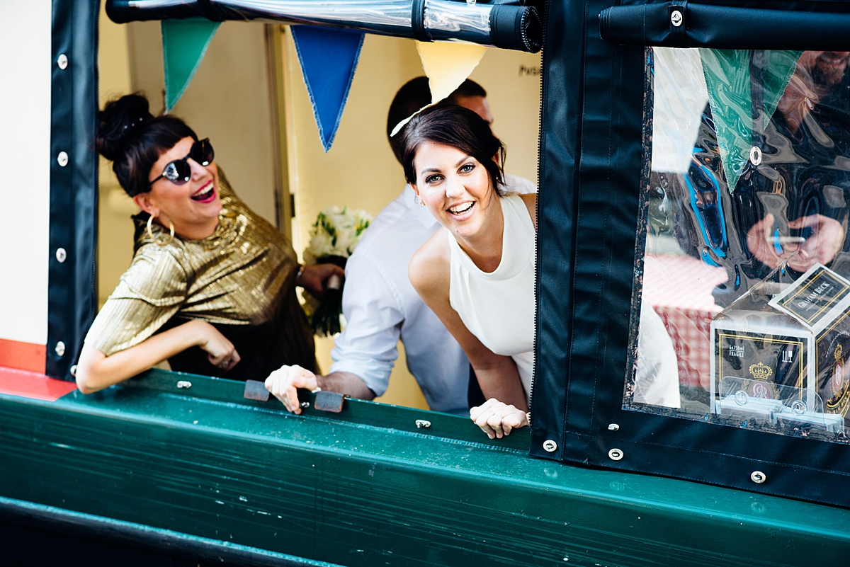 Bride and guests on a canal boat heading to a Shoreditch warehouse Wedding. Image by Parrot & Pineapple Wedding Photography.