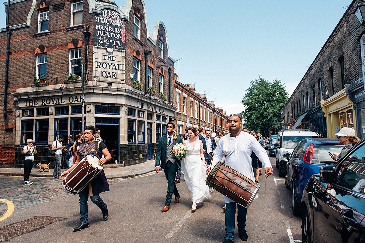 dhol drummers procession up colombia road for hackney town hall wedding