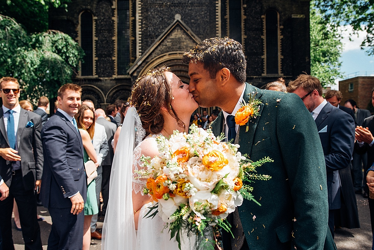 Bride and groom kiss outside church covered in confetti. Image by london wedding photographer Parrot and pineapple.