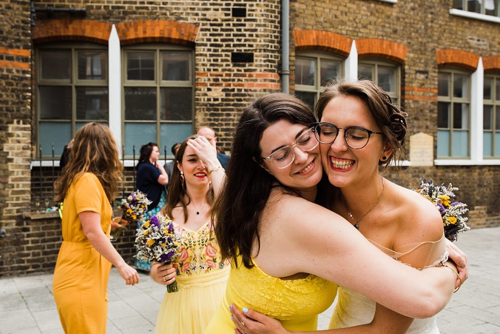 Bride hugs bridesmaid. Image in wedding blog post how to choose your wedding photographer