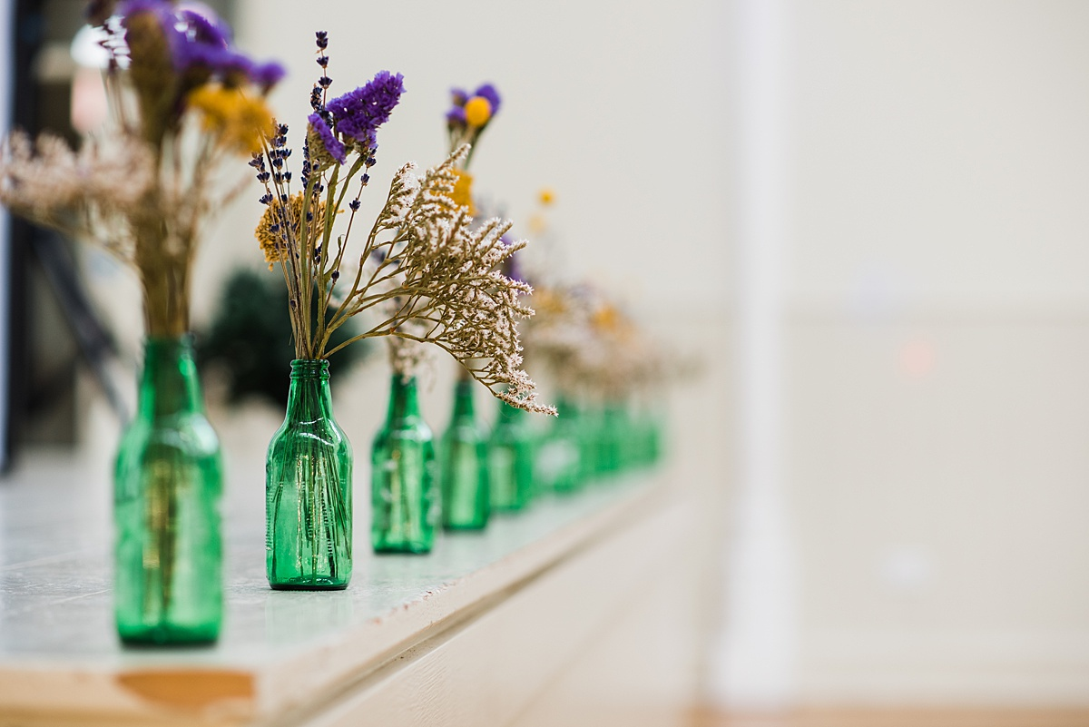 Green bottles with dried flowers on wedding breakfast table taken by Parrot & Pineapple Wedding Photography