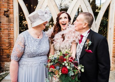 Bride poses with her parents and laughs. Image by informal wedding photographer Parrot and Pineapple.