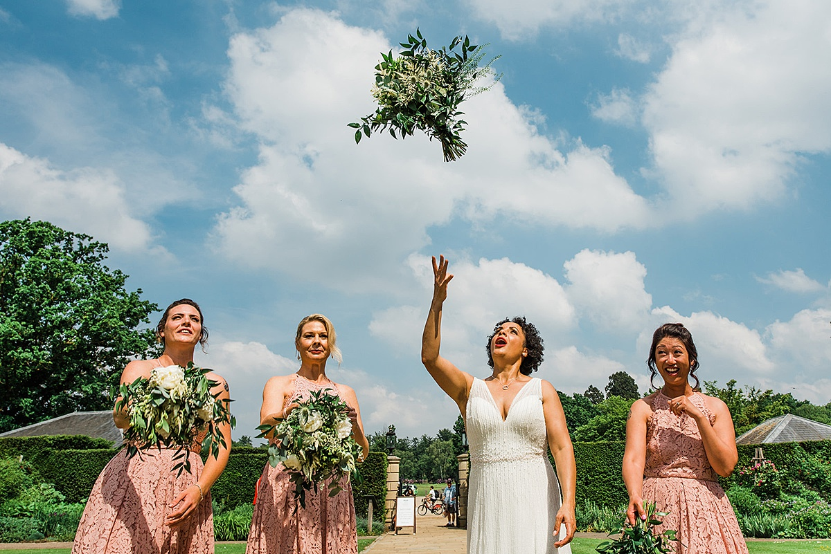 Bride throws her bouquet in the air surrounded by 3 bridesmaids. Photograph by feminist wedding photographer Parrot & Pineapple