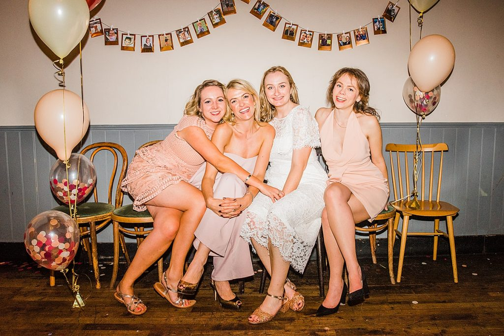 Bride and bridesmaids huddled together at a wedding. Image by informal wedding photographer Parrot & Pineapple.