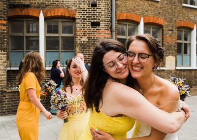 Bride hugs bridesmaid. Feminist wedding photographer. Image by Parrot & Pineapple Wedding Photography.