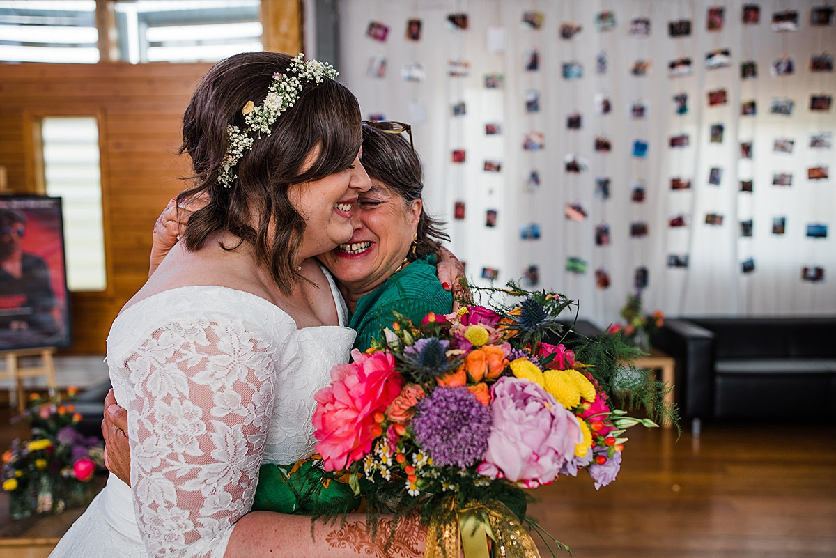 Bride hugs her mum while holding a rainbow coloured bouquet. Image by relaxed wedding photographer Parrot and Pineapple.