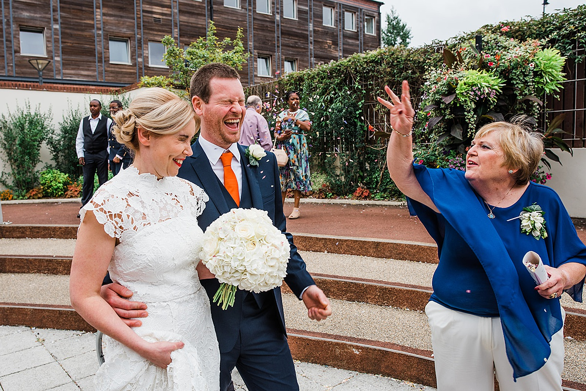 Lady throws confetti over bride and groom. Bride holds simple white round bouquet. Image by fun wedding photographer Parrot and Pineapple Wedding Photography.
