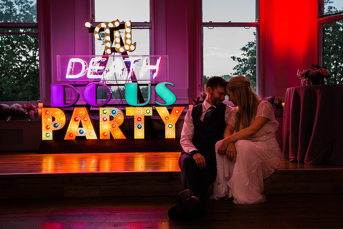 Couple in front of till death us do party sign