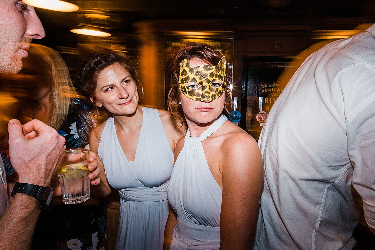 Bridesmaid wearing giraffe mask at fun wedding party. Image by informal wedding photographer Parrot and Pineapple.