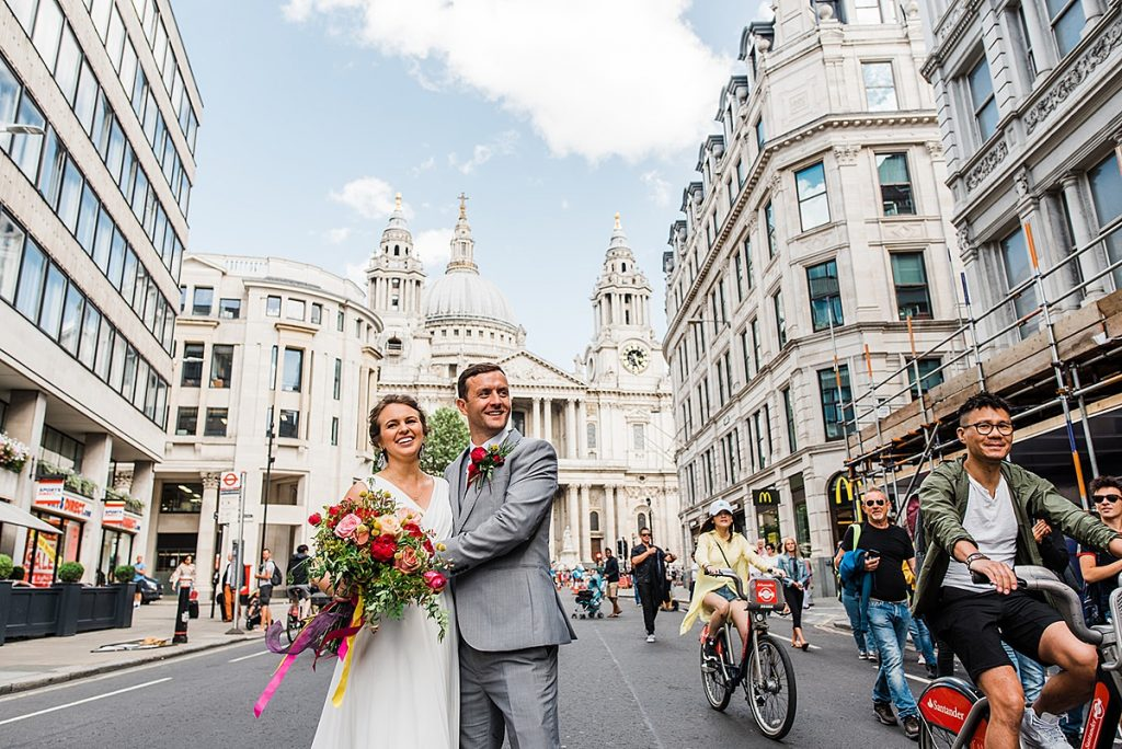 Bride and groom stand in front of St Pauls Cathedral. Image by informal wedding photographer Parrot and Pineapple Wedding Photography.
