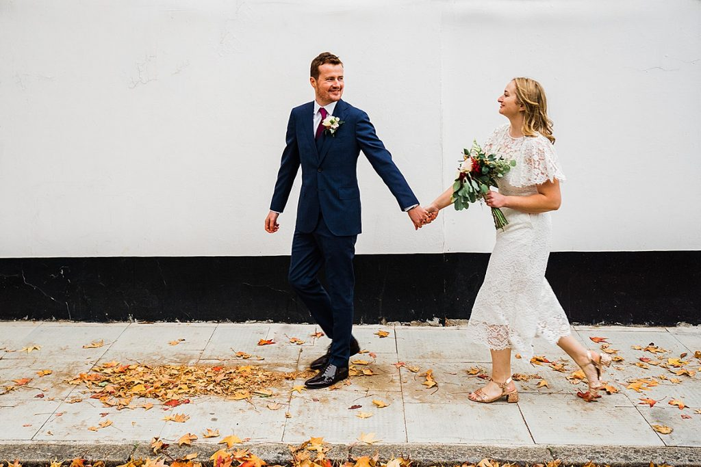 Groom leads bride in jumpsuit along path covered in leaves.