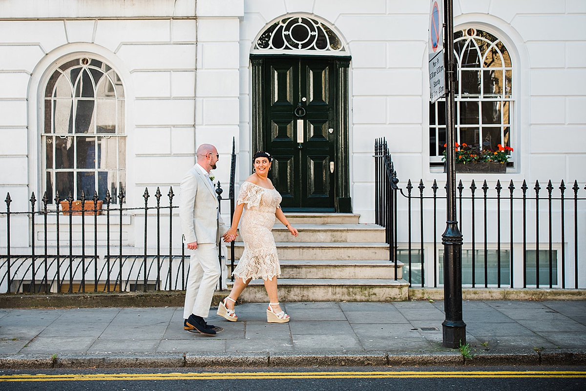 Bride and groom walk along city street after Islington Town Hall wedding. Image by Parrot and Pineapple.