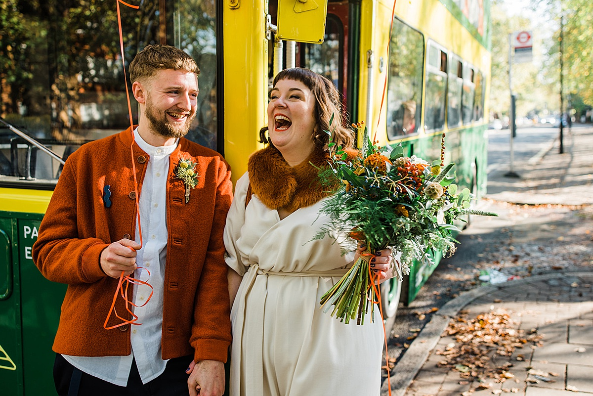 Bride and groom stand next to double decker bus laughing. Brides holds bouquet. Image by Parrot & Pineapple Wedding Photography. Informal wedding photographer.