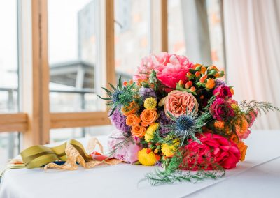 Rainbow bright wedding bouquet lying on a table. Image by Parrot and Pineapple Wedding Photography.