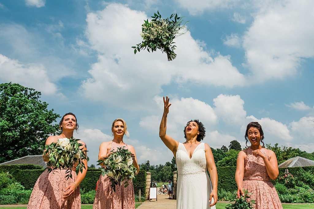 bride bridesmaids toss greenery bouquet. Informal wedding photography by Parrot and Pineapple - wedding planning advice