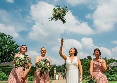 bride bridesmaids toss greenery bouquet. Informal wedding photography by Parrot and Pineapple