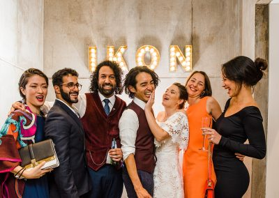 Bride groom and friends stand in front of light up IKON sign at Ikon gallery wedding in Birmingham