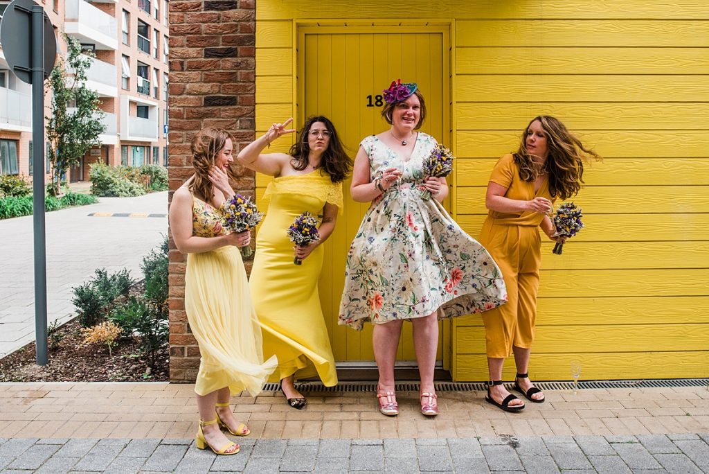 4 bridesmaids wearing yellow stand against a yellow wall