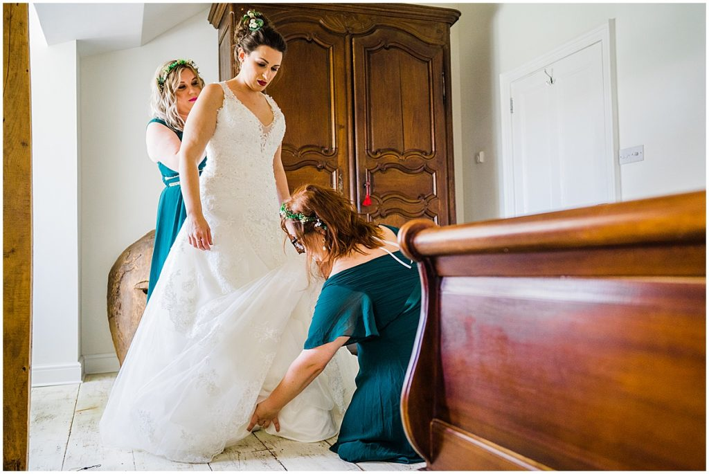 bride is helped in to her wedding dress by two bridesmaids wearing green at anran farm wedding
