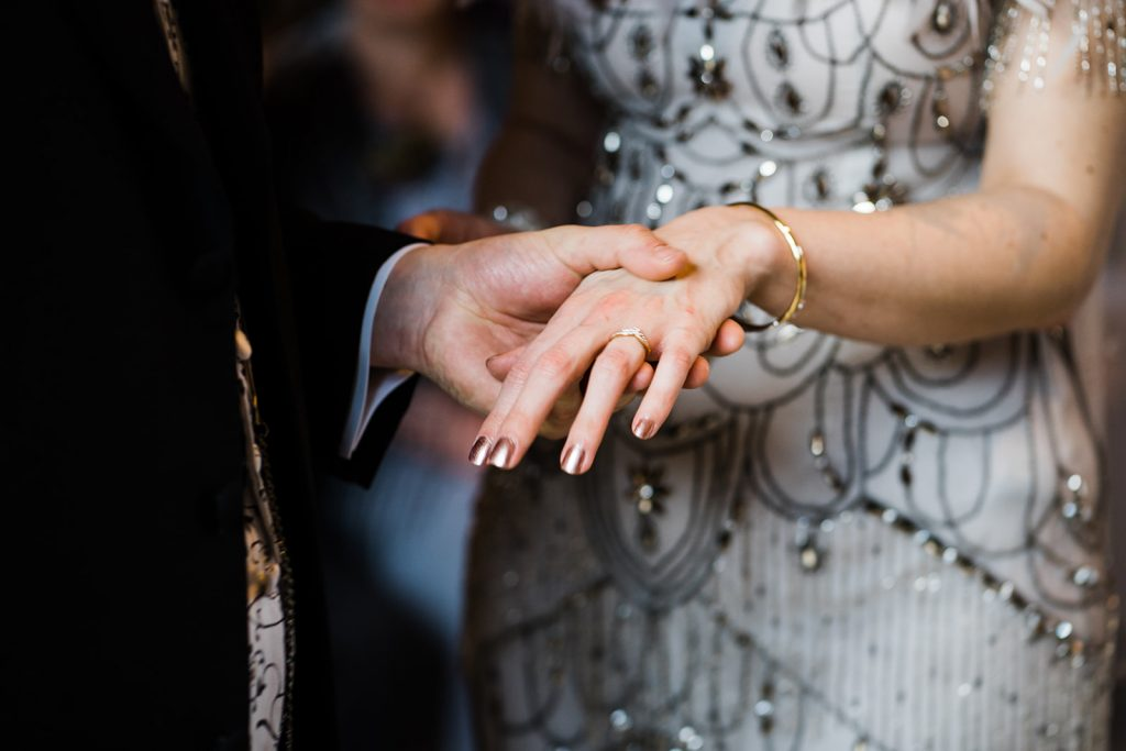 How to select your wedding rings. Groom places ring on brides finger at winter wedding. Image by Parrot and pIneapple