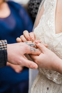 Brides slides wedding ring on to tattooed groom. Image by Parrot and Pineapple Wedding Photography