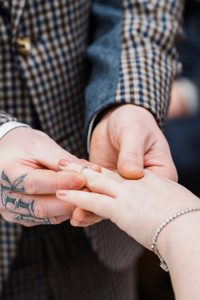 Tattooed groom slides ring on to brides finger - Image by Parrot and Pineapple Wedding Photography