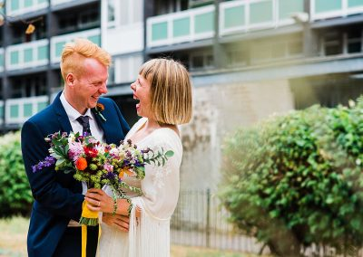 bride and groom stand in front of city tower block hugging and laughing