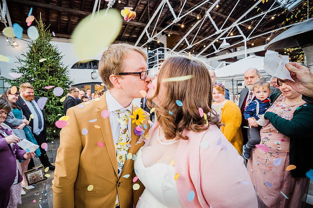 Bride and groom showered in colourful confetti outside The Bond Company Birmingham wedding venue in Digbeth