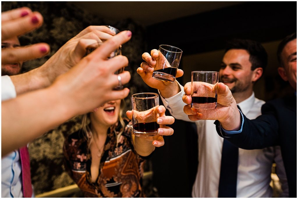 Wedding guests holding shots all reach in to clink glasses