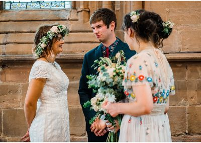 Bride-and-Groom-at-front-of-Temple-Balsall-Church-DIY-Home-Garden-Wedding-Parrot-and-Pineapple-Wedding-Photography