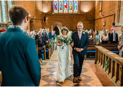 Bride-walking-down-the-ailse-Temple-Balsall-Church-DIY-Home-Garden-Wedding-Parrot-and-Pineapple-Wedding-Photography
