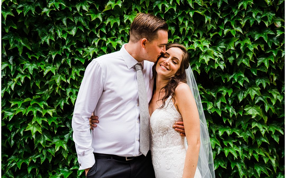 Standing in front of a wall of ivy the groom kisses bride and hugs her at Bay Tree Hotel wedding in Oxfordshire