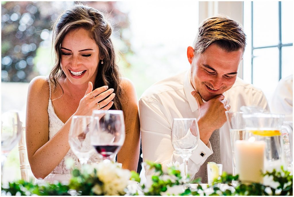 bride and groom laugh at wedding speeches sitting at table
