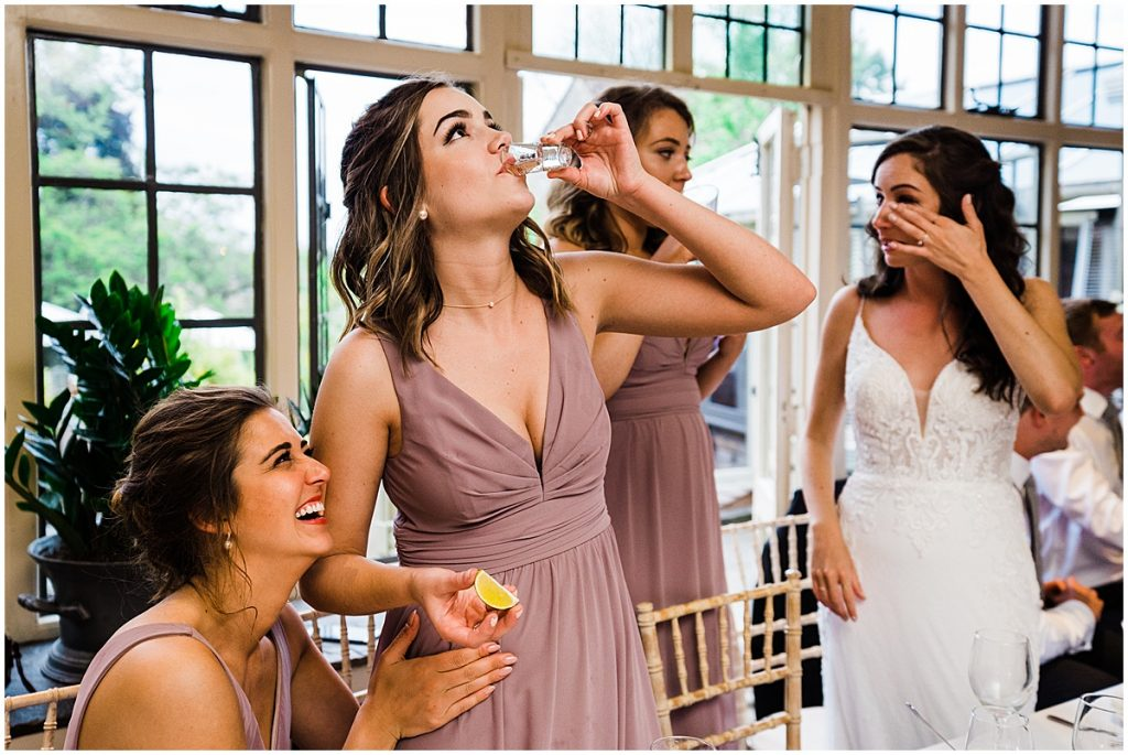 Bridesmaid drinks shot surrounded by other bridesmaids and bride at Oxfordshire wedding