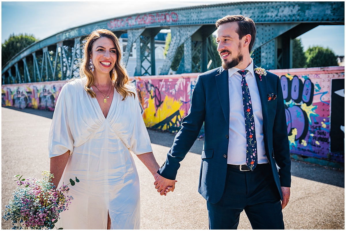 bride and groom walk hand in hand over grafitti covered bridge in london after small wedding ceremony
