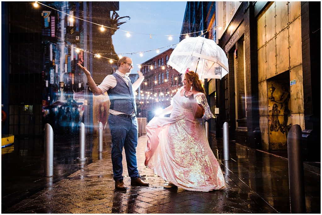 bride wearing sequin wedding dress dances with groom in the rain under umbrella at digbeth birmingham wedding