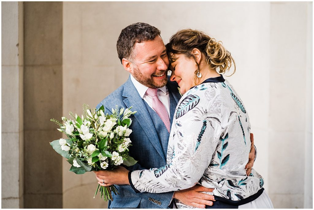 bride hugs in to groom holding bouquet and wearing a bridal bomber jacket at marylebone town hall wedding