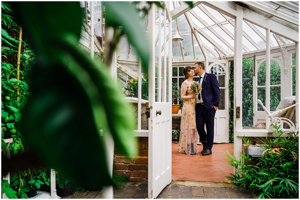 groom kisses bride on the cheek standing in victorian greenhouse and yeldersley hall wedding