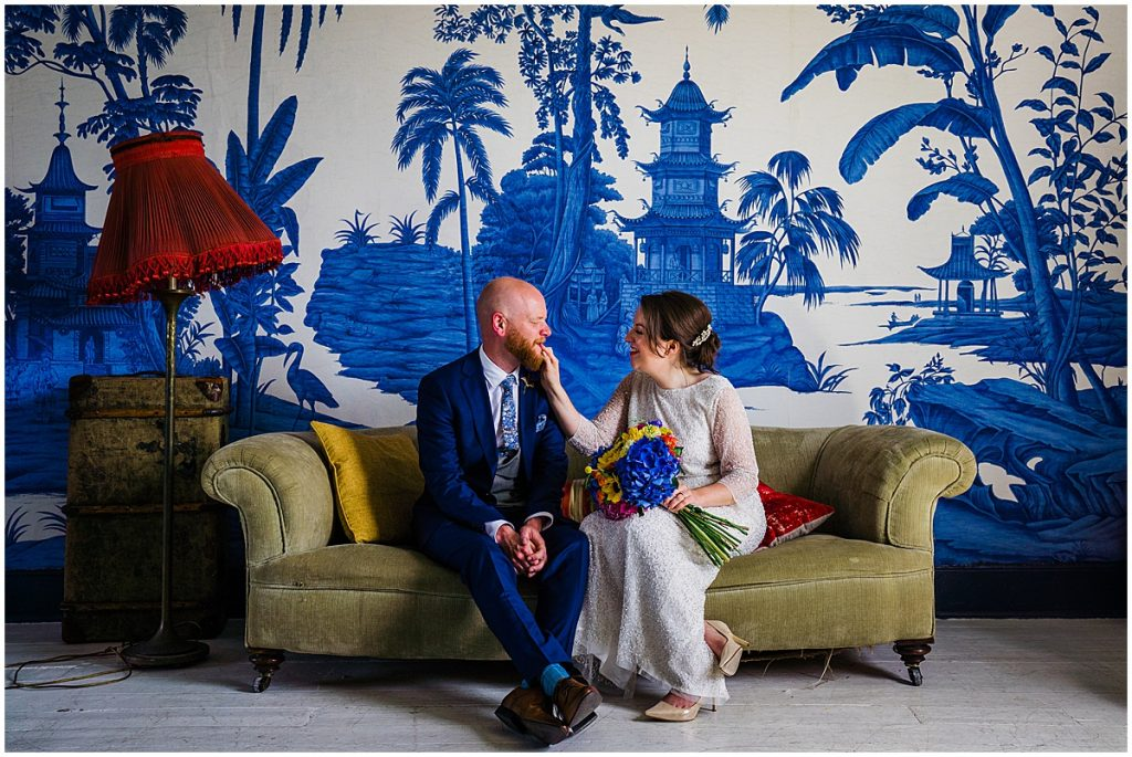 bride and groom sit on sofa at The Roost - london wedding venue - wedding planning advice