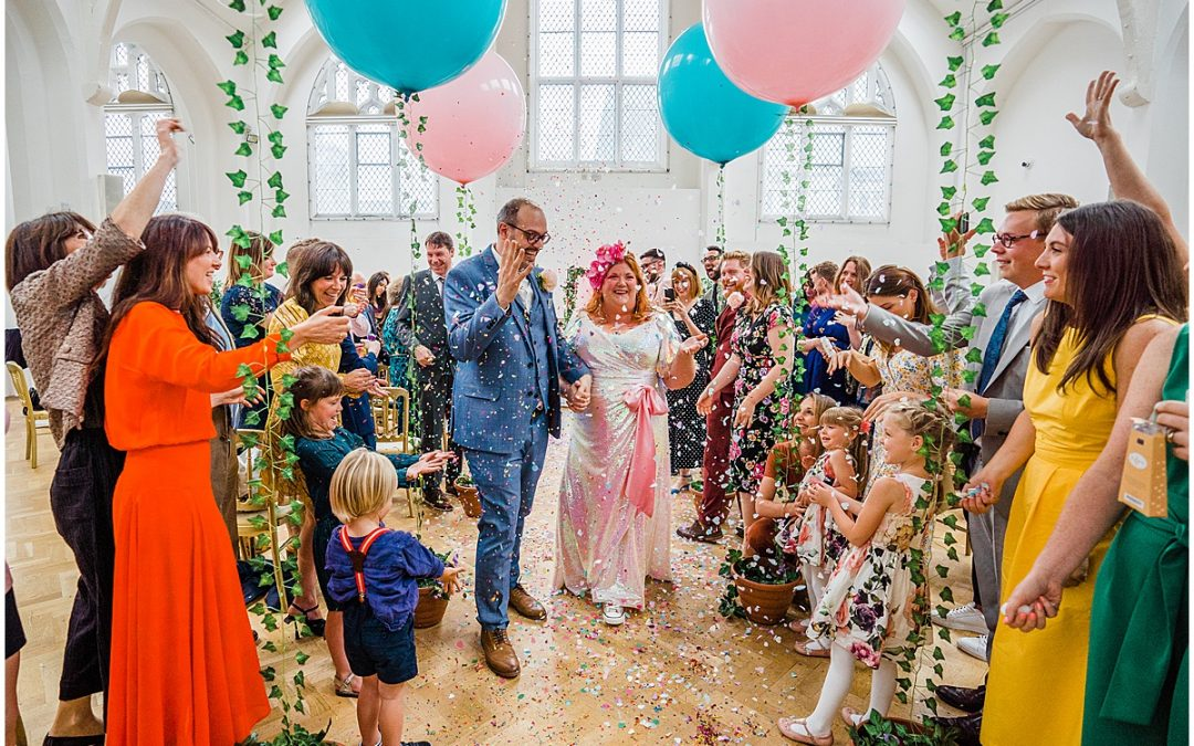 bride in sequin dress walks with groom through confetti shower at Old Library wedding in Birmingham