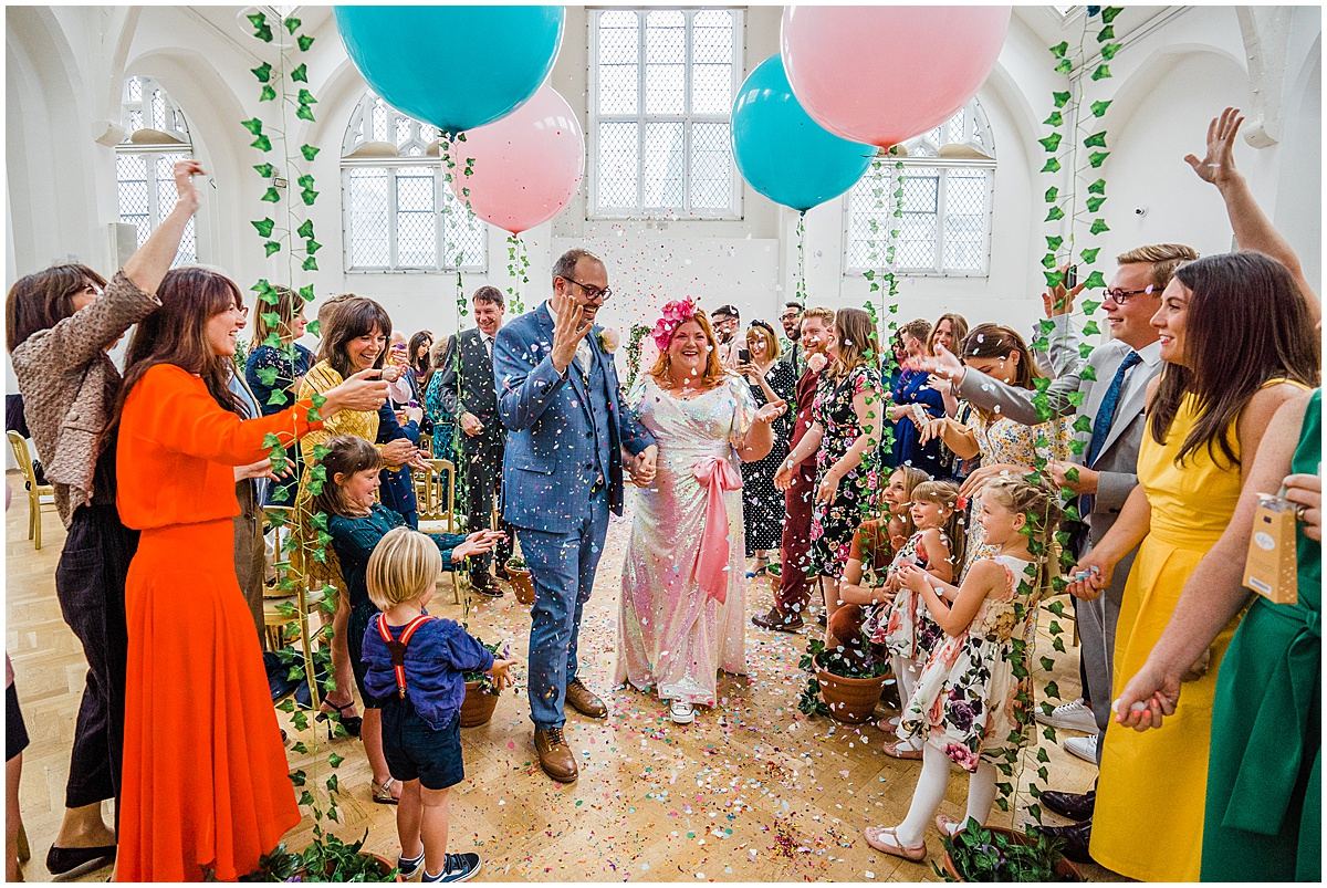 Bride and groom walk through colourful confetti at birmingham wedding venue The Old Library in Digbeth