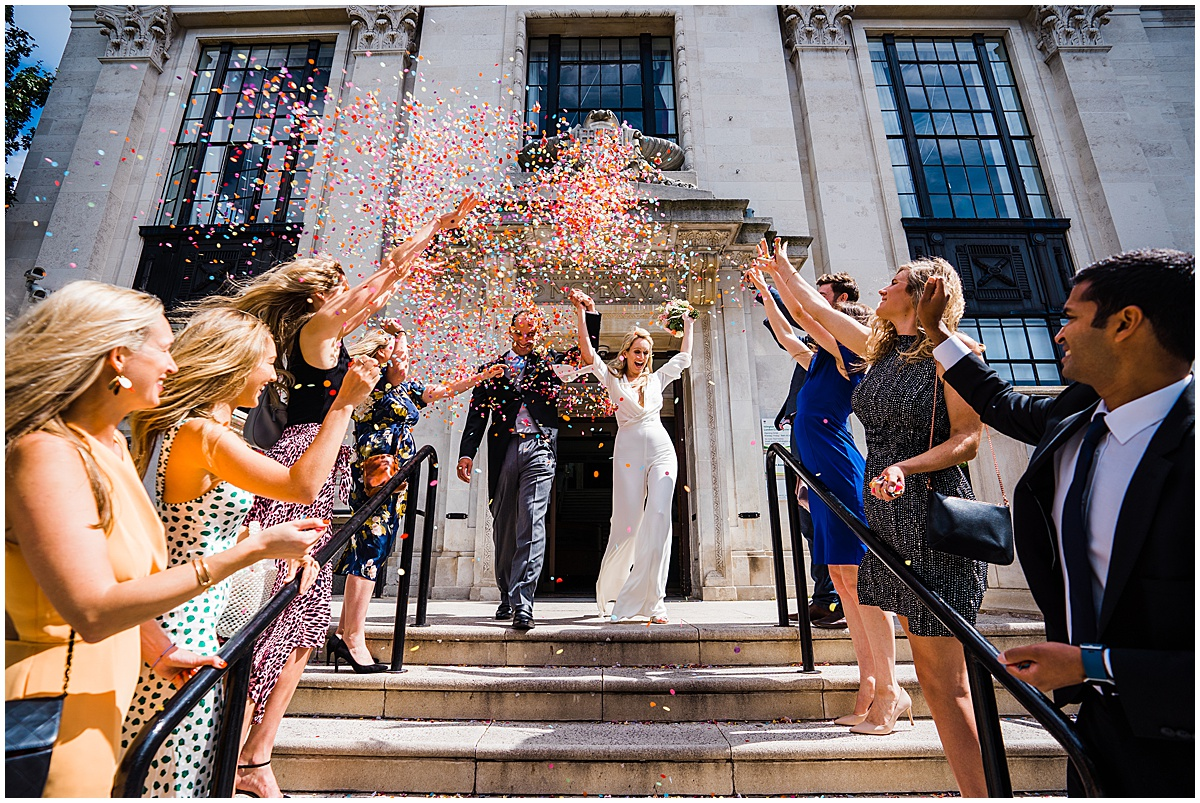 bride in jumpsuit holds hands in the air with groom as they walk down islington town hall registry office steps under shower of confetti at small wedding