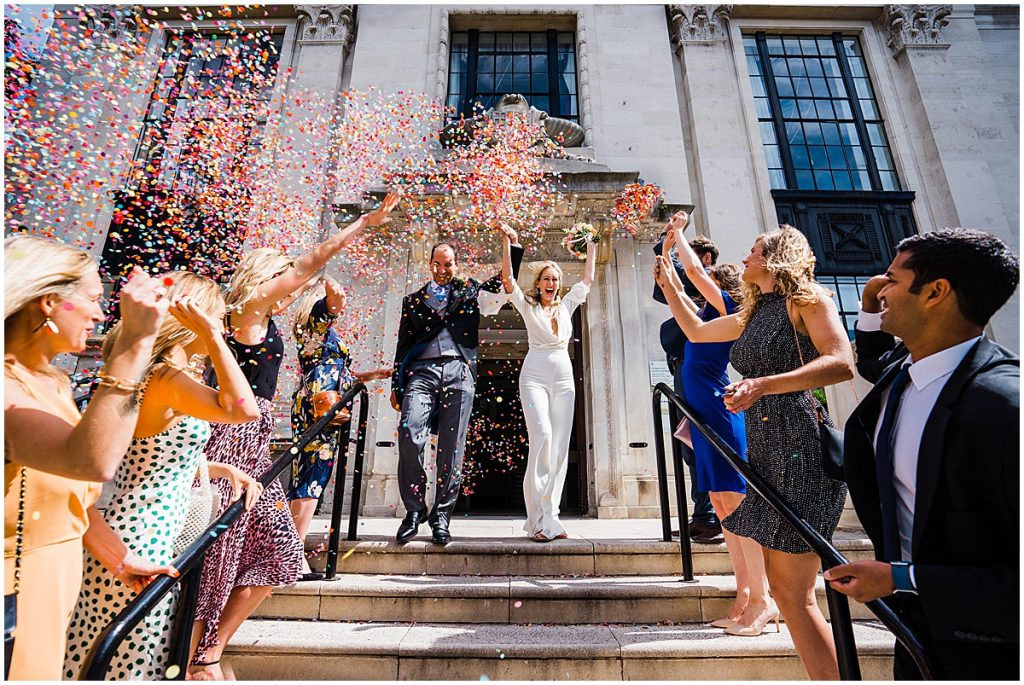 bride and groom hold hands in the air while walking down steps at islington town hall getting showered in confetti