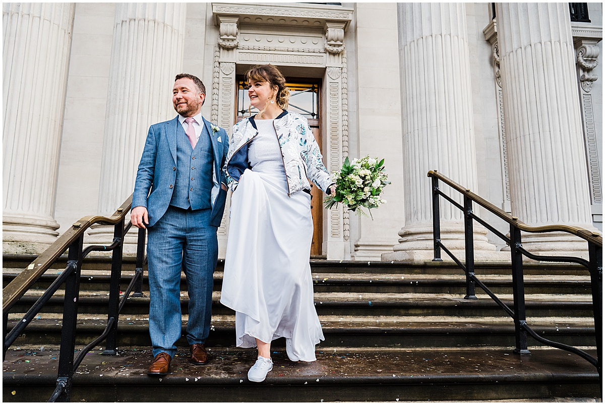 Bride and groom walk down steps at old marylebone town hall after small wedding ceremony in london