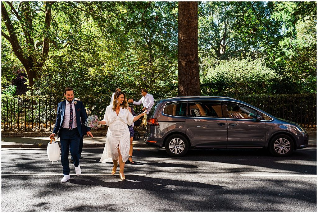 bride and groom walk across a city road to a registry office wedding after being dropped off by a taxi