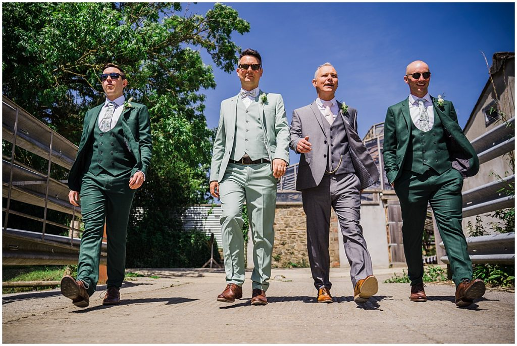 4 men wearing green wedding suits stride towards the camera.