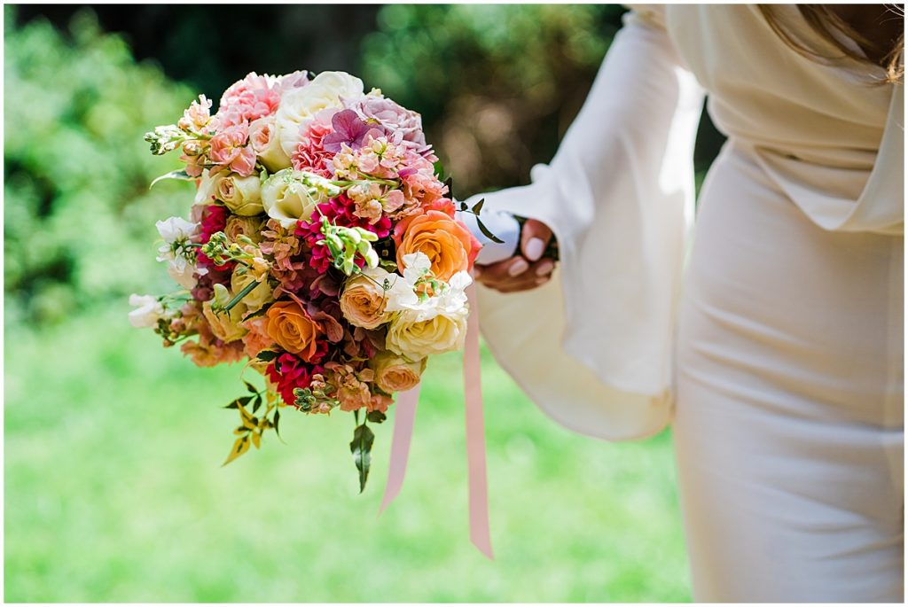 brightly coloured bridal bouquet with pink, yellow, orange and white flowers held by bride wearing white bridal jumpsuit from les heroines