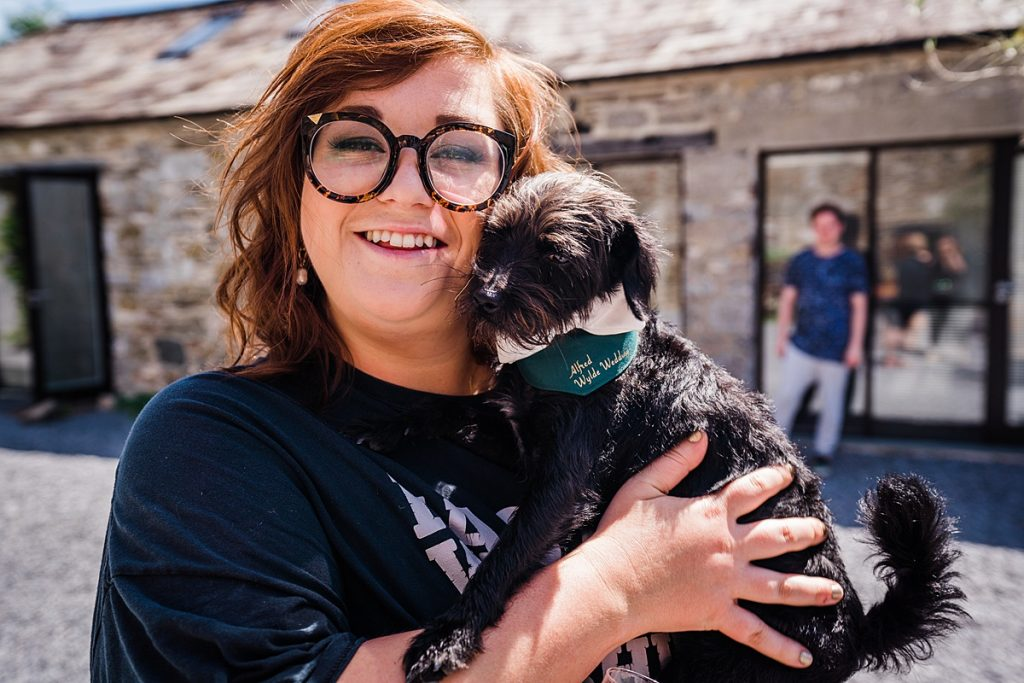 woman in glasses hold small black dog